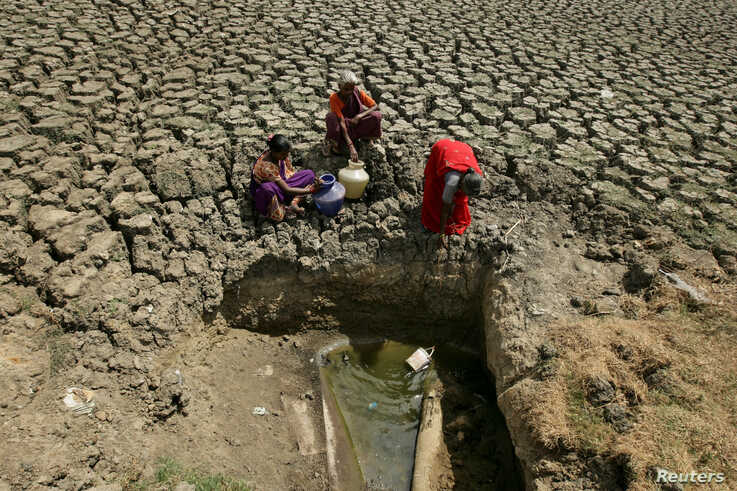 Women fetch water from an opening at a dried-up lake in Chennai, India.