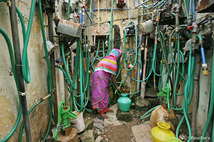 A woman uses a hand pump to fill up a container with drinking water in Chennai, India.