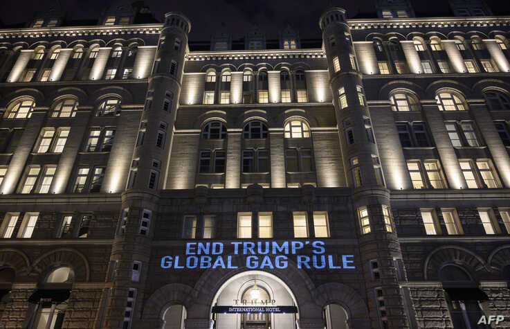Activists from the Population Connection Action Fund project a message onto the Trump International Hotel, to protest the global gag rule, Washington, Jan. 23, 2019.