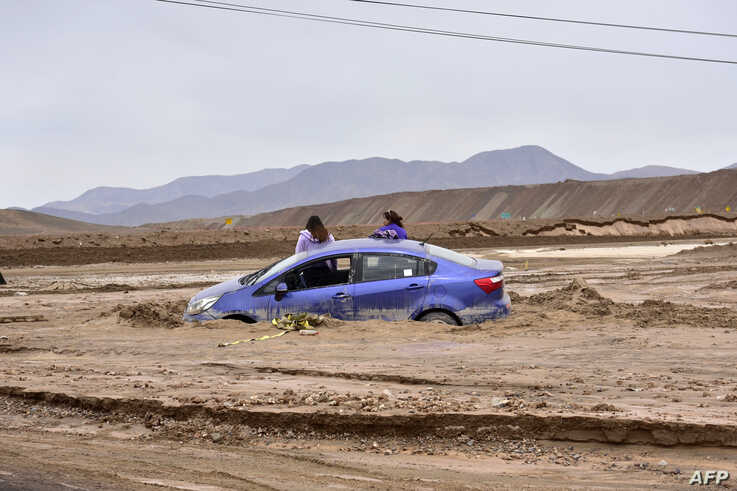 FILE - A car is trapped in mud due to floods near a copper mine in Chuquicamata, Chile, Feb. 7, 2019.