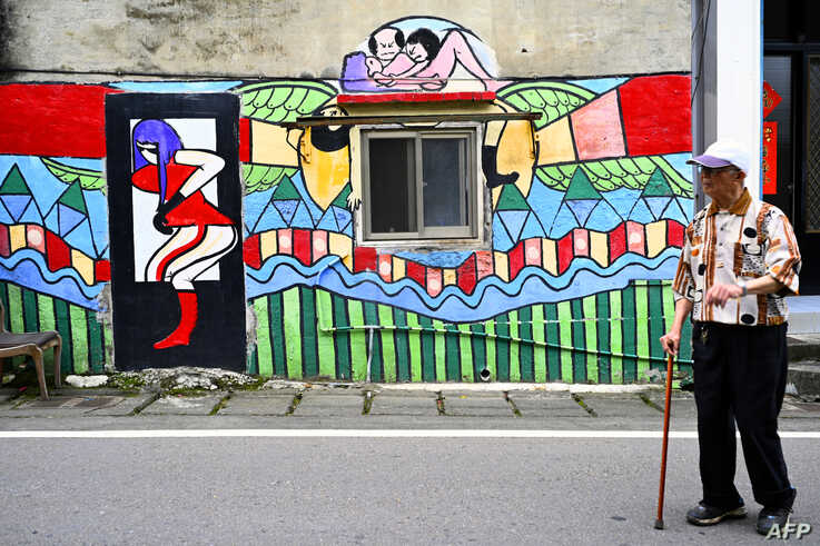 A local resident walks past a wall painted by Hakka graffiti artist Wu Tsun-hsien in the Taiwanese village of Ruan Chiao, March 30, 2019.