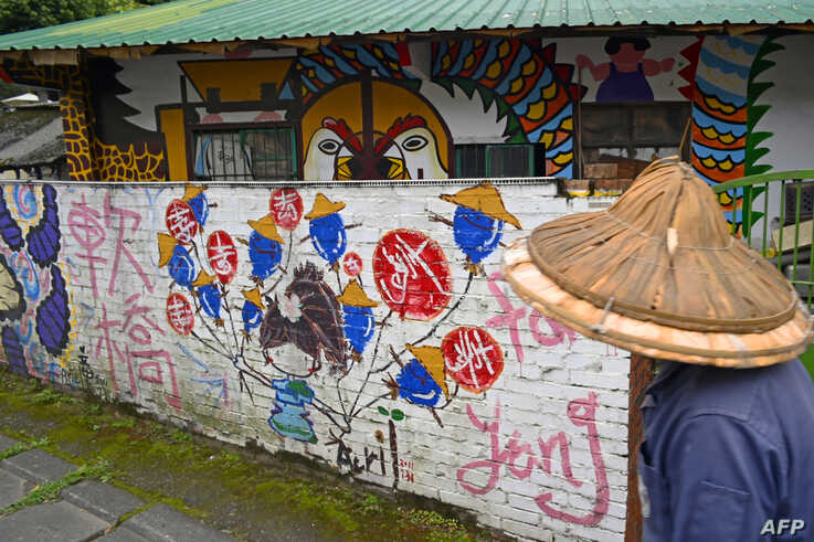 A local resident walks past a house painted by Hakka graffiti artist Wu Tsun-hsien in the Taiwanese village of Ruan Chiao, March 30, 2019.