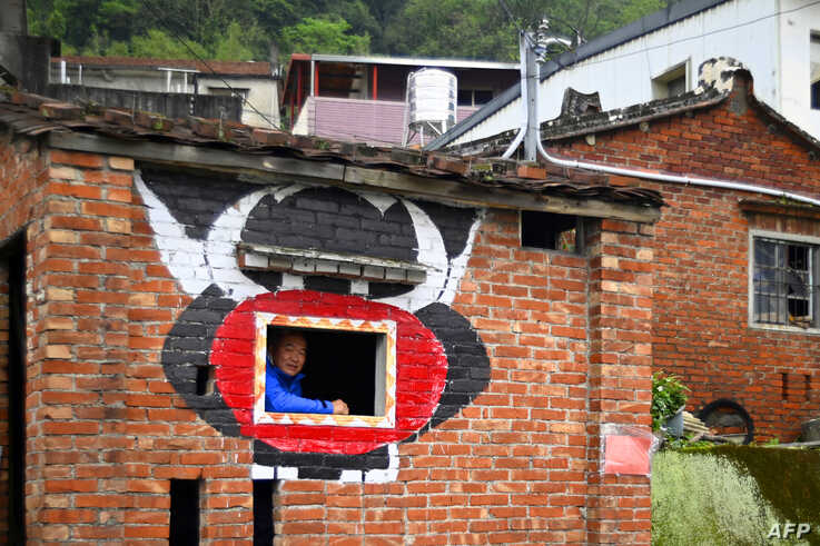 Hakka graffiti painter Wu Tsun-hsien poses in an empty old house near his home in the Taiwanese village of Ruan Chiao. The village is virtually devoid of young people, but Wu Tsun-hsien is coaxing the Instagram generation back by transforming local homes into a canvas of color.