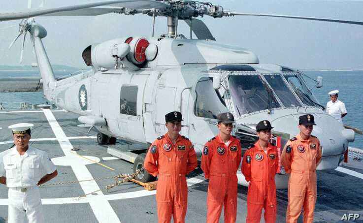 FILE - Four Taiwanese naval pilots posed for a group portrait in front of a U.S.-made S-70 C anti-submarine helicopter onboard the Chengkong, a Taiwanese frigate which docked in Penghu naval base, Aug. 20, 1999.