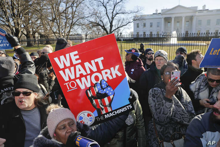 Union members and other federal employees stop in front of the White House in Washington during a rally to call for an end to the partial government shutdown, Jan. 10, 2019.
