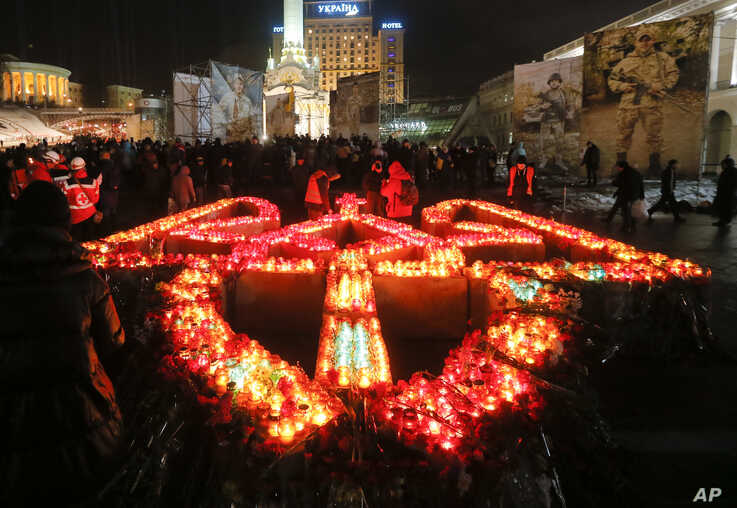 FILE - People light candles placed in the shape of Ukraine's coat of arms, to pay tribute to the victims of the 2013-2014 anti-government protests called the Revolution of Dignity, during commemoration events in central Kiev, Ukraine, Feb. 20, 2017.