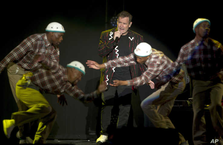 "In this photo taken Saturday, July 2017, South African musician Johnny Clegg, middle, and the dancers perform during ""The Final Journey"" concert at the Grand Arena in Cape Town, South Africa."
