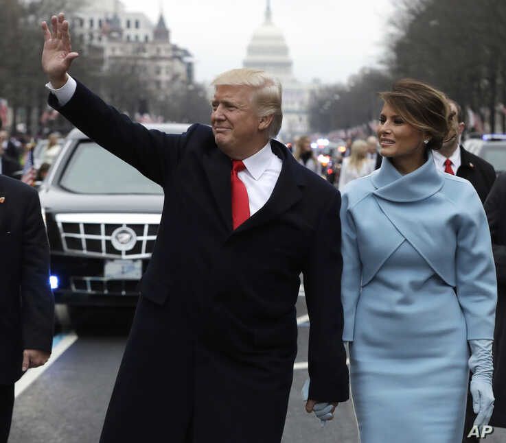 FILE - President Donald Trump waves as he walks with first lady Melania Trump during the inauguration parade on Pennsylvania Avenue in Washington, Jan. 20, 2017.