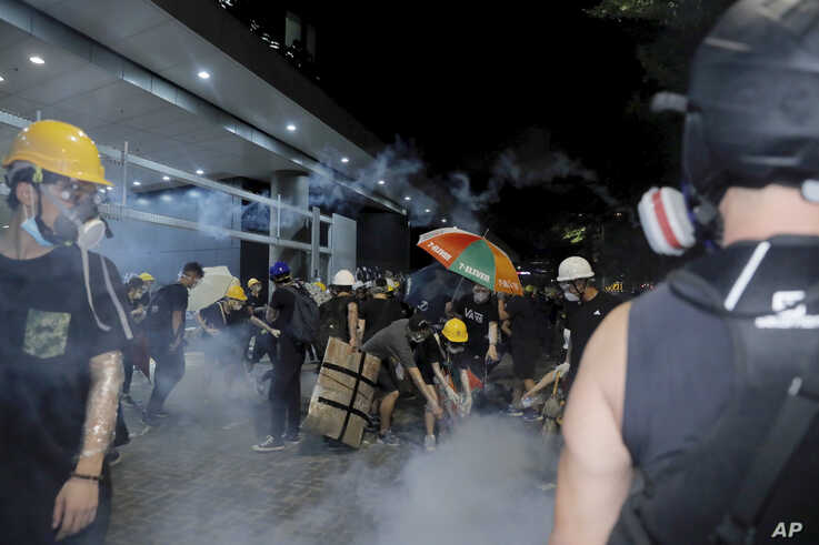 Protesters pour water on tear gas canisters at the Legislative Council in Hong Kong, during the early hours  on July 2, 2019.