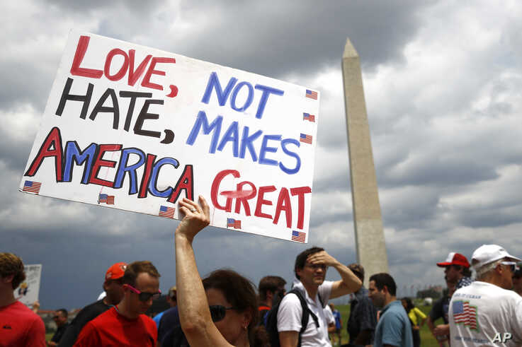 Kathleen Otal, of Arlington, Va., holds up a sign before Independence Day celebrations on the National Mall in Washington, July 4, 2019.