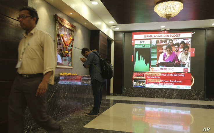 A man offers prayer to a Hindu goddess at the Bombay Stock Exchange (BSE) office, as India's Finance Minister Nirmala Sitharaman is seen on a television screen presenting the annual budget in Mumbai, India, July 5, 2019.