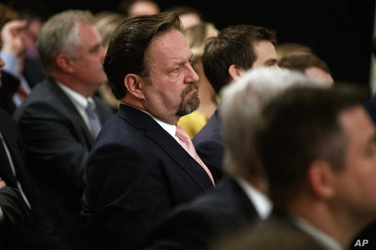 Radio host Sebastian Gorka listens as President Donald Trump speaks during the Social Media Summit in the East Room of the White House, July 11, 2019.