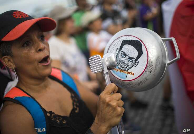 """FILE - A demonstrator bangs on a pot that has a cartoon drawing of Governor Ricardo Rossello and text the reads in Spanish """"Quit Ricky"""" in San Juan, Puerto Rico, July 19, 2019."""