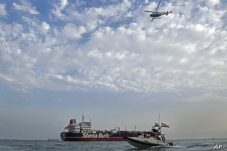A speedboat and a helicopter of the Iran's Revolutionary Guard move around a British-flagged oil tanker Stena Impero, which was seized by the Guard, in the Iranian port of Bandar Abbas, July 21, 2019.