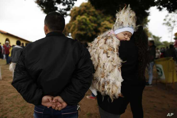 Jesus Cardozo Servin sleeps on his mother's shoulder dressed in a feathered costume during a Mass in honor of St. Francis Solano in Emboscada, Paraguay, July 24, 2019.