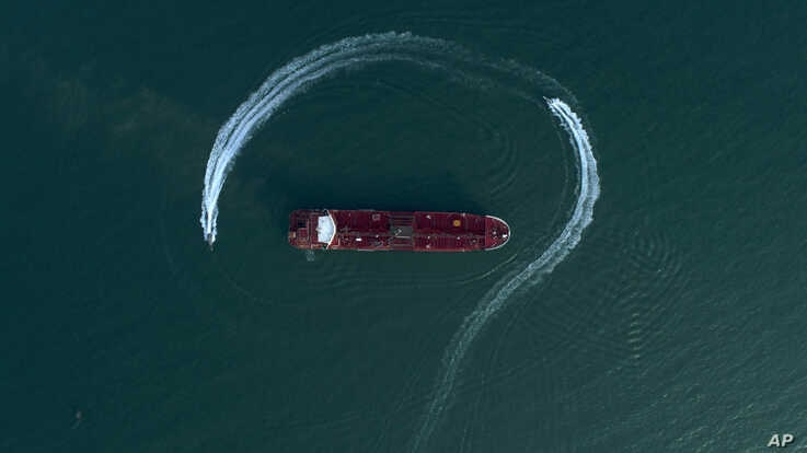 In this July 21, 2019 photo, an aerial view shows a speedboat of Iran's Revolutionary Guard moving around the British-flagged oil tanker Stena Impero which was seized in the Strait of Hormuz by the Guard, in the Iranian port of Bandar Abbas.