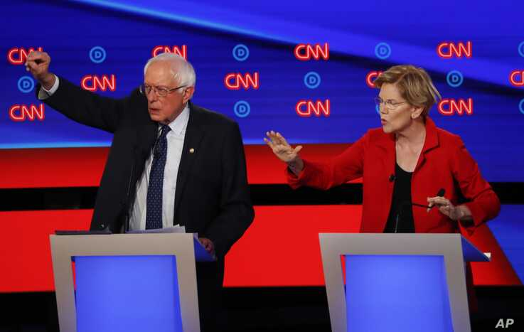 Sen. Bernie Sanders, I-Vt., and Sen. Elizabeth Warren, D-Mass., talk during in the first of two Democratic presidential primary debates hosted by CNN in the Fox Theatre in Detroit, July 30, 2019.
