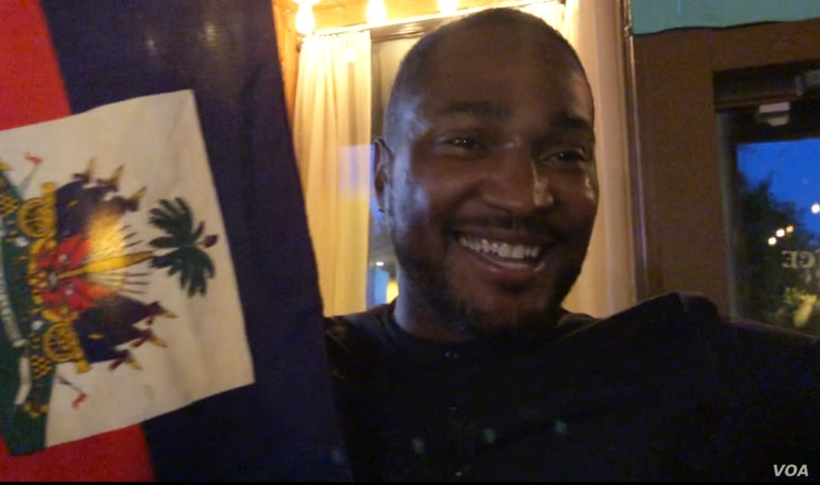 This Haitian soccer fan danced and waved the Haitian flag at Port-au-Prince restaurant in Washington after the team's 3-2 victory over Canada. (S. Lemaire/VOA)