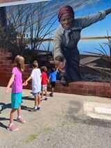 Harriet Tubman reaches out, extending a hand over an unfinished brick wall to draw the viewer into the coastal wetlands beyond. A little girl reached back. Her grandparents posted the image. Soon, it was everywhere. (Courtesy/Downtown Cambridge)