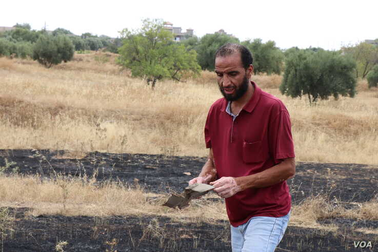 Ossama, a father of four, picks up bits of a rocket that hit farmland the night after Tripoli forces re-took the town from Khalifa Haftar's Libyan National Army, in Gharyan, Libya, June 28, 2019. (H.Murdock/VOA)