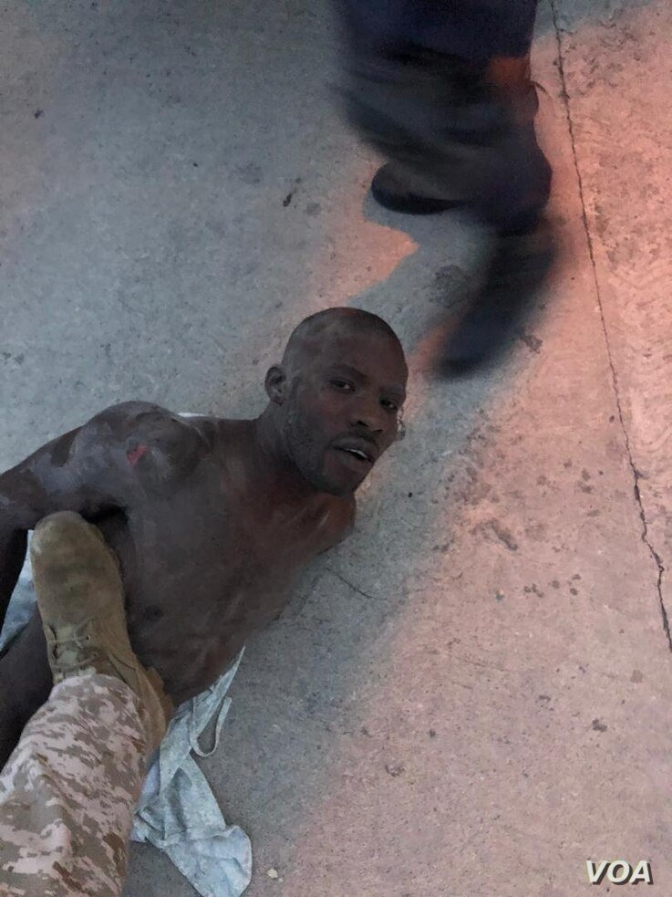 Alleged gang leader Arnel Joseph lies on the ground as police. puts boot on his chest