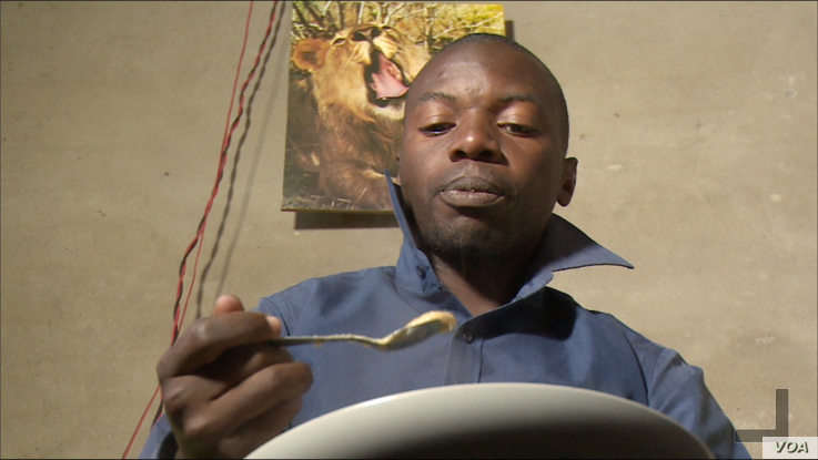 Munyaradzi Masiiwa, having porridge for breakfast at his home in Harare on July 23, 2019,  as he cannot afford a loaf of bread due to high cost of living in Zimbabwe.