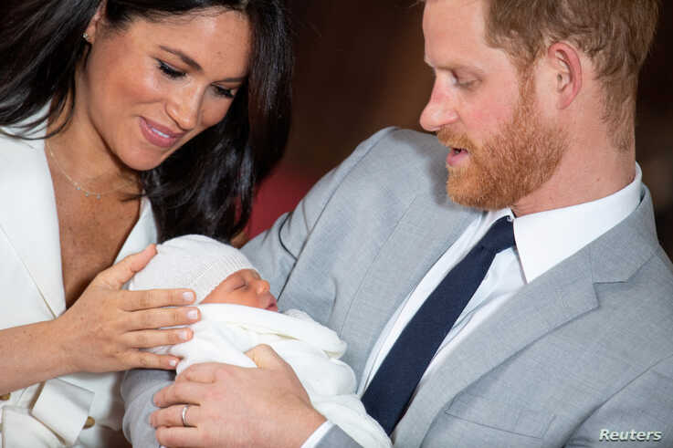 Britain's Prince Harry and Meghan, Duchess of Sussex hold their baby son during a photocall in St George's Hall at Windsor Castle, in Berkshire, Britain May 8, 2019.