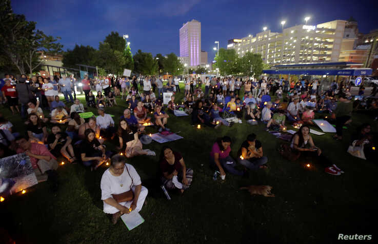"People with candles attend as immigration rights activists hold a ""Lights for Liberty"" candlelit vigil at Cleveland Square Park in El Paso, Texas,  July 12, 2019."