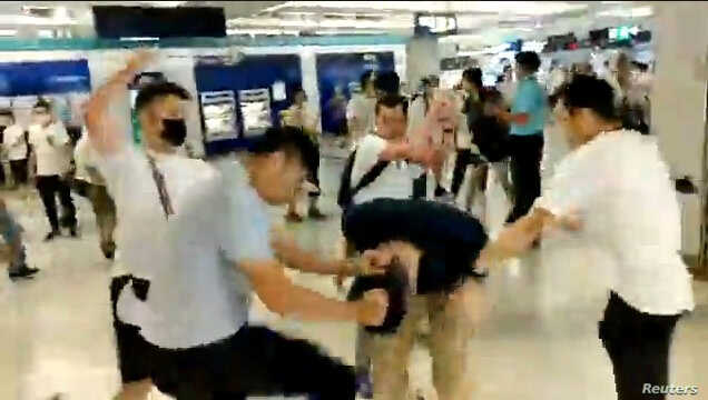 Men in white T-shirts and face masks attack anti-extradition bill demonstrators and reporters at a train station in Hong Kong, China, July 21, 2019, in this still image obtained from a social media live video.