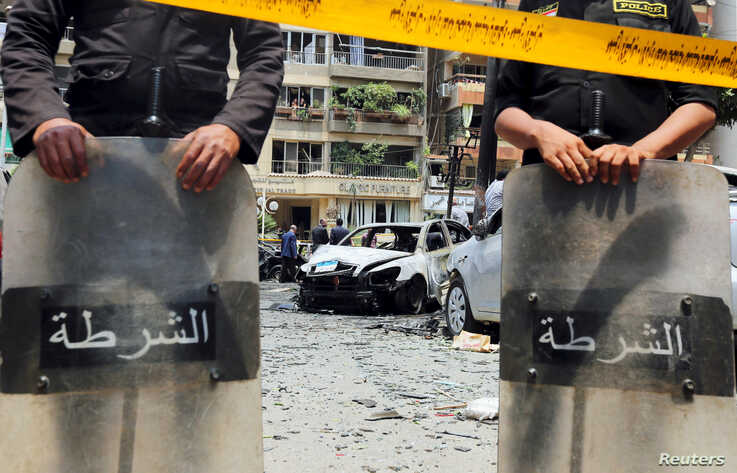 FILE - Policemen investigate the site of a car bomb attack on the convoy of Egyptian public prosecutor Hisham Barakat near his house at Heliopolis district in Cairo, Egypt, June 29, 2015.