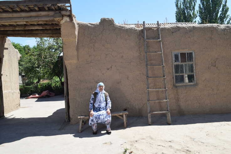 """Aziz Isa Elkun's mother sits in front of her house in Xinjiang, China, April 2019, in this scene from the film """"An Unanswered Telephone Call"""" (Courtesy Aziz Isa Elkun)"""