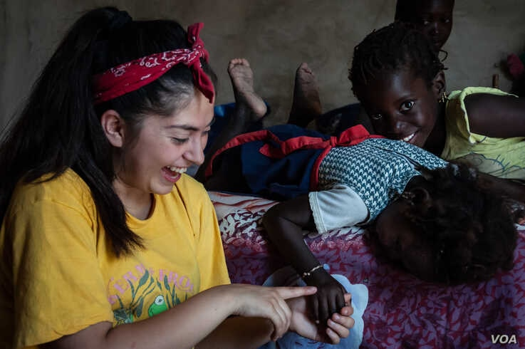 Teresa Topete, a rising junior at Lick-Wilmerding High School in San Francisco, plays with her host family in the village of Guedj Martin, Senegal. (Annika Hammerschlag, for VOA)