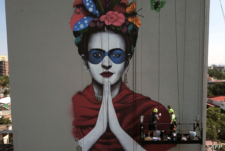 """Irish urban artist Fin Dac (2-R) and his assistant work on his mural """"Magdalena"""", in honor of Mexican painter Magdalena Carmen Frida Kahlo in the month of her birth, in Guadalajara, Jalisco state, July 9, 2019."""