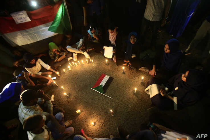 Sudanese protesters take part in a vigil in the capital Khartoum to mourn dozens of demonstrators killed in a brutal raid on a Khartoum protest, July 13, 2019.