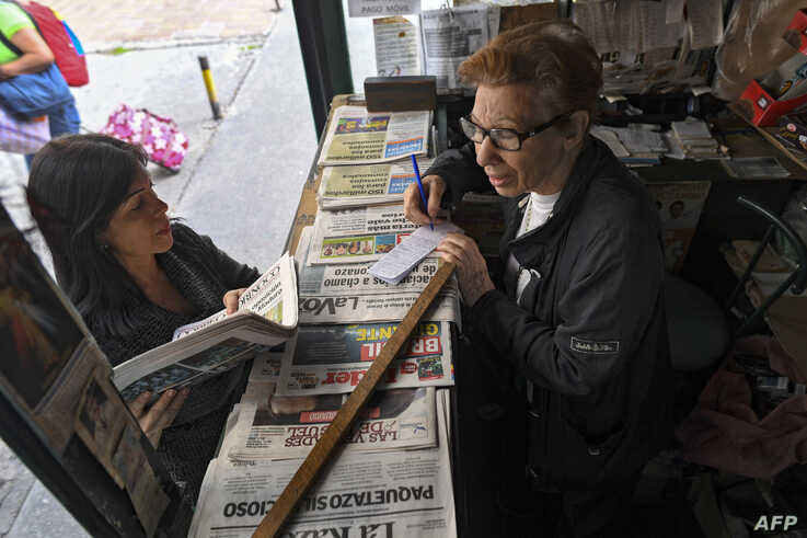 FILE - A woman buys printed newspapers at a kiosk in Caracas, Venezuela, July 3, 2019.