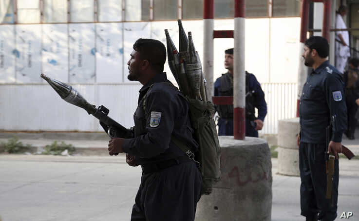 Afghan security personnel stand guard at the site of a deadly attack in Kabul. Officials say the political offices of the president's running mate were hit by a large explosion and stormed by an unknown number of attackers.