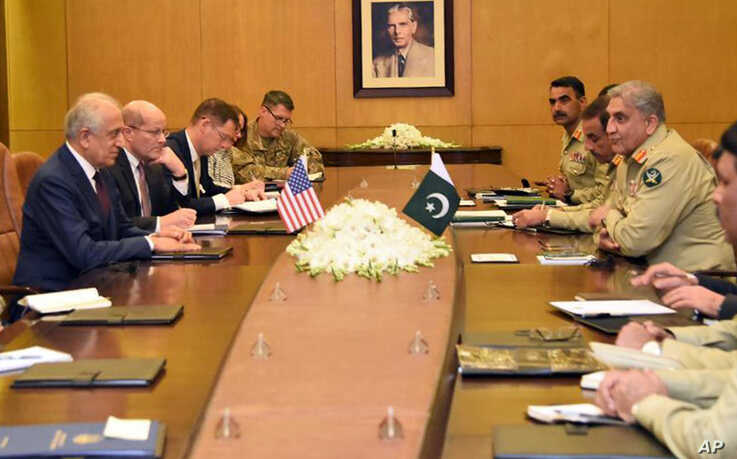 In this photo released by Inter Services Public Relations of Pakistan's military, U.S. peace envoy Zalmay Khalilzad, left, talks with Pakistani Army Chief Gen. Qamar Javed Bajwa, second from right, during a meeting in Rawalpindi, Pakistan, Jan. 17, 2019.