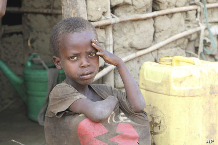 A young boy sits outside his small house in a village on the outskirts of Burundi capital Bujumbura, July 6, 2019.