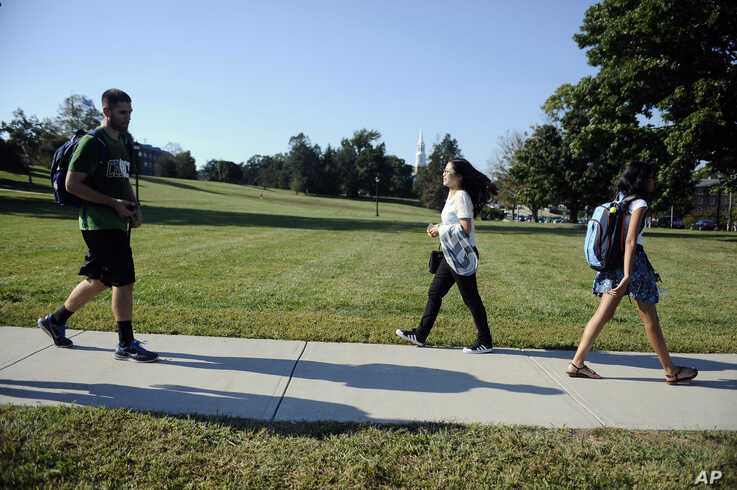 A student from China, center, walks on campus at the University of Connecticut,  in Storrs, Connecticut, Sept. 18, 2015.