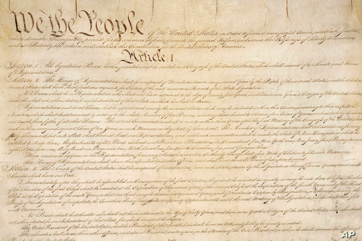This photo made available by the U.S. National Archives shows a portion of the first page of the United States Constitution.