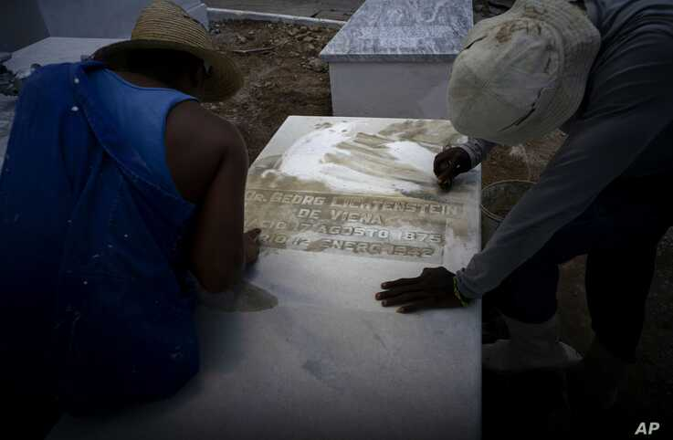 Workers clean the top of a tomb at the Jewish cemetery in Guanabacoa, eastern Havana, Cuba, June 12, 2019.