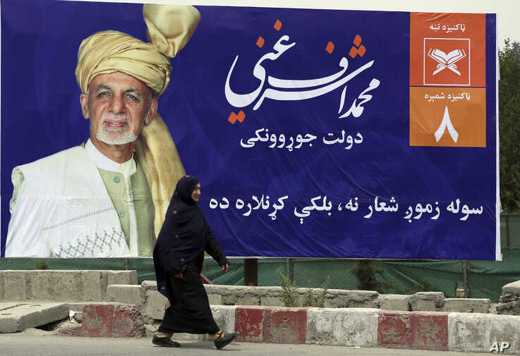 An Afghan woman walks past an election poster of current president and presidential candidate Ashraf Ghani during the first day of campaigning in Kabul, Afghanistan, July 28, 2019.