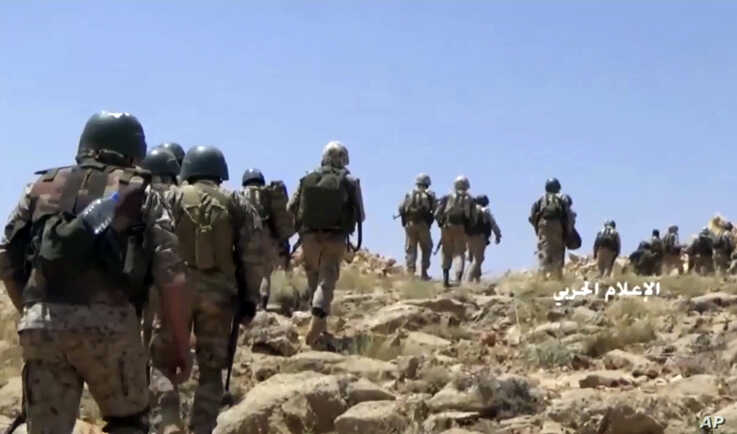 This frame grab from video released July 22, 2017, and provided by the government-controlled Syrian Central Military Media, shows Hezbollah fighters advancing up a hill in an area on the Lebanon-Syria border.
