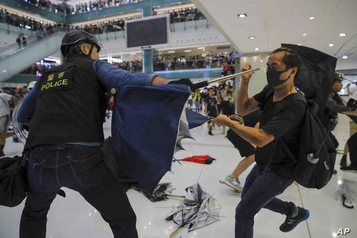 A policeman scuffles with a protester inside a mall in Sha Tin District in Hong Kong, July 14, 2019.