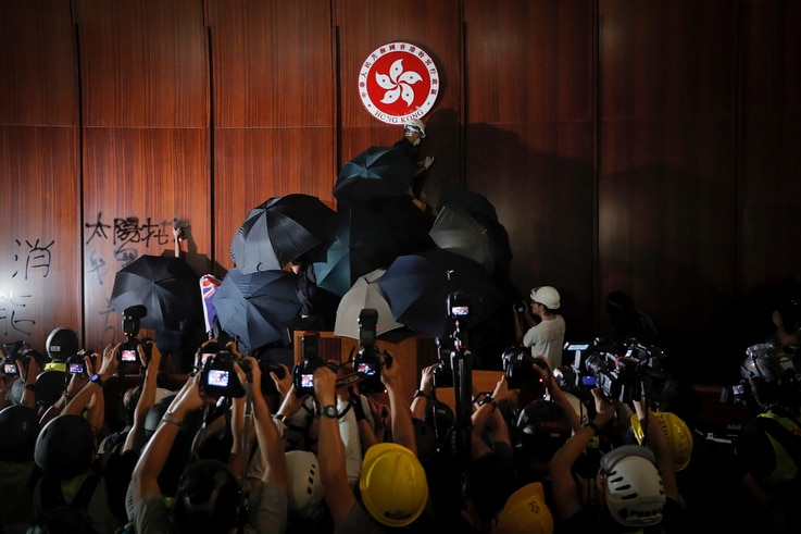 Journalists film a protester defaces the Hong Kong emblem inside the meeting hall of the Legislative Council in Hong Kong.