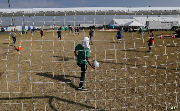 Migrants play soccer at the U.S. government's newest holding center for migrant children in Carrizo Springs, Texas, July 9, 2019.