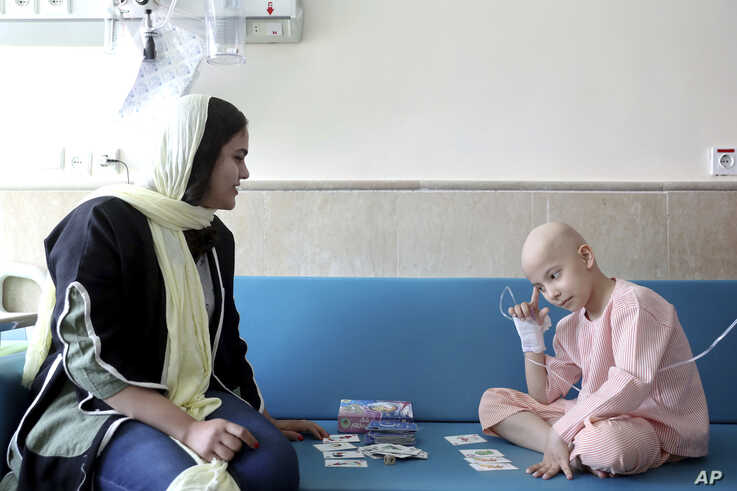 Taha Shakouri, an 8-year-old boy suffering from liver cancer, plays cards at Mahak Children's Hospital in Tehran, Iran, June 19, 2019.