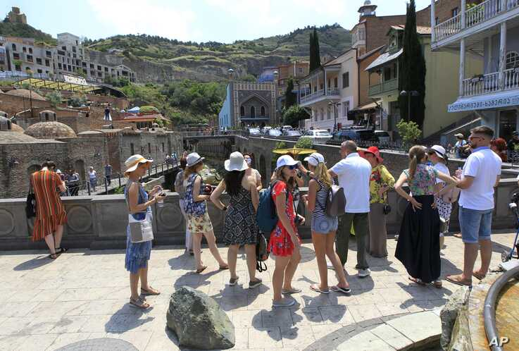 FILE -  A group of Russian tourists listen to a guide in the Old Town section of Tbilisi, Georgia, June 22, 2019.