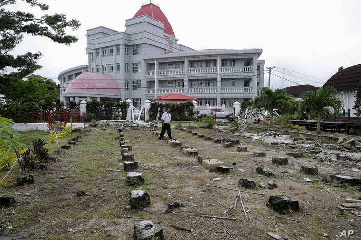 FILE - A security guard walks outside the Tonga's historic Parliament House destroyed last year in Cyclone Gita in Nuku'alofa, April 10, 2019.