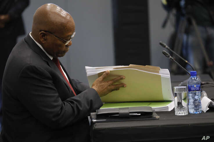 Former South African president Jacob Zuma leafs through documents as he testifies before a state commission probing wide-ranging allegations of corruption in government and state-owned companies, in Johannesburg, South Africa, July 17, 2019.